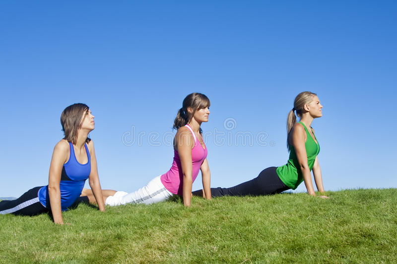 Yoga, Exercise and Healthy living. Three beautiful women stretching together during their morning exercise and yoga routine royalty free stock photography
