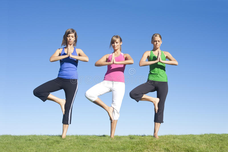 Yoga and Exercise Women. A group of three attractive women exercising and doing early morning yoga together stock images