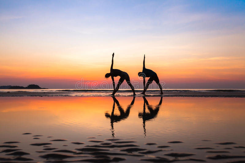 Yoga exercises, silhouettes of couple stock images