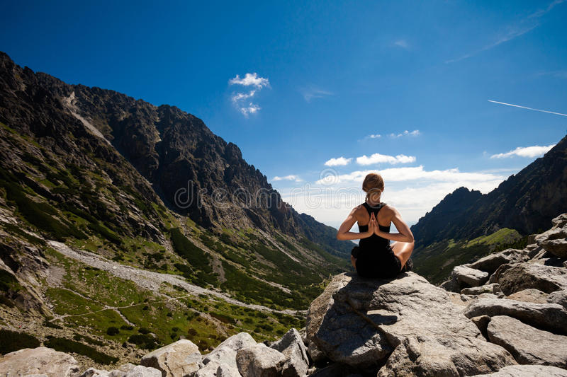 Yoga exercising in Tatry mountains. Exercise yoga everywhere - in slovakian Tatry mountains. Beautiful panorama - Chata Teryho, kotlina Piatich Spišských royalty free stock images