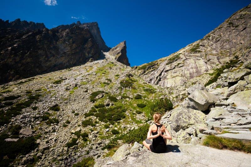 Yoga exercising in Tatry mountains. Exercise yoga everywhere - in slovakian Tatry mountains. Beautiful panorama - Chata Teryho, kotlina Piatich Spisskych plies royalty free stock photo