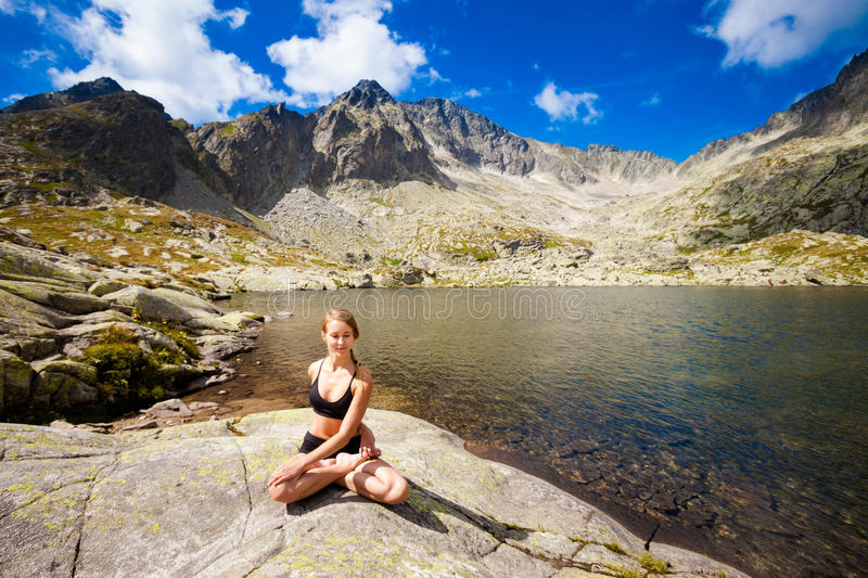 Yoga exercising in Tatry mountains. Exercise yoga everywhere - in slovakian Tatry mountains. Beautiful panorama - Chata Teryho, kotlina Piatich Spisskych plies royalty free stock image