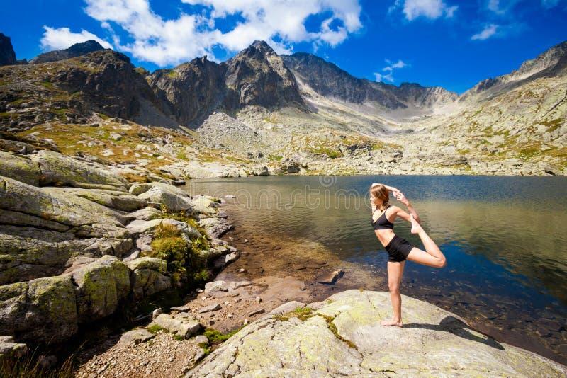 Yoga exercising in Tatry mountains. Exercise yoga everywhere - in slovakian Tatry mountains. Beautiful panorama - Chata Teryho, kotlina Piatich Spisskych plies royalty free stock photos