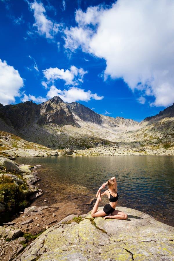 Yoga exercising in Tatry mountains. Exercise yoga everywhere - in slovakian Tatry mountains. Beautiful panorama - Chata Teryho, kotlina Piatich Spisskych plies stock photo