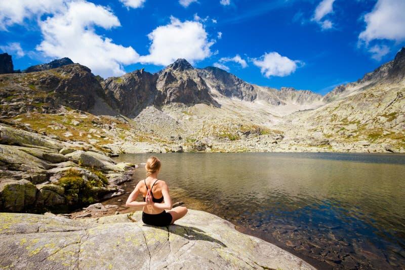 Yoga exercising in Tatry mountains. Exercise yoga everywhere - in slovakian Tatry mountains. Beautiful panorama - Chata Teryho, kotlina Piatich Spisskych plies stock photos