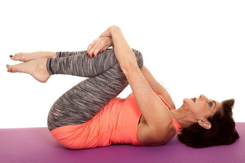 Yoga för äldre kvinna på tillbaka krullningsknä royaltyfria bilder