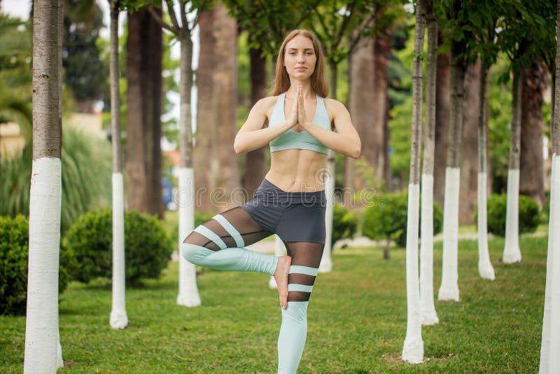 Yoga för övning för yogalärarekvinna i stad parkerar i otta arkivfoto