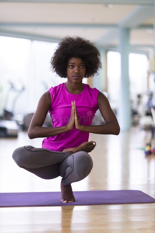Yoga för afrikansk amerikankvinnaövning i idrottshall arkivfoton
