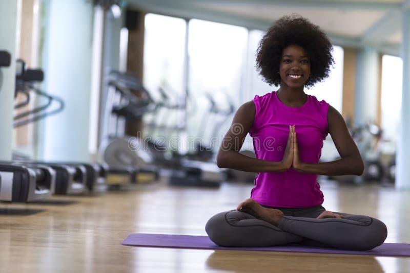 Yoga för afrikansk amerikankvinnaövning i idrottshall royaltyfri foto