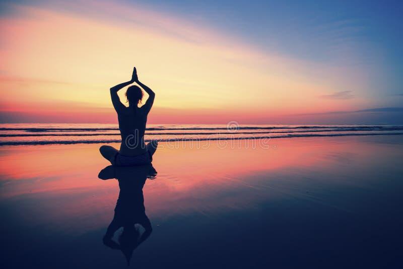 Yoga för ung kvinna för kontur praktiserande på havsstranden på den surrealistiska solnedgången Natur arkivbilder