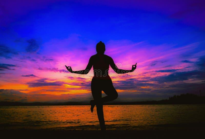 Yoga för ung kvinna för kontur praktiserande på stranden royaltyfri foto