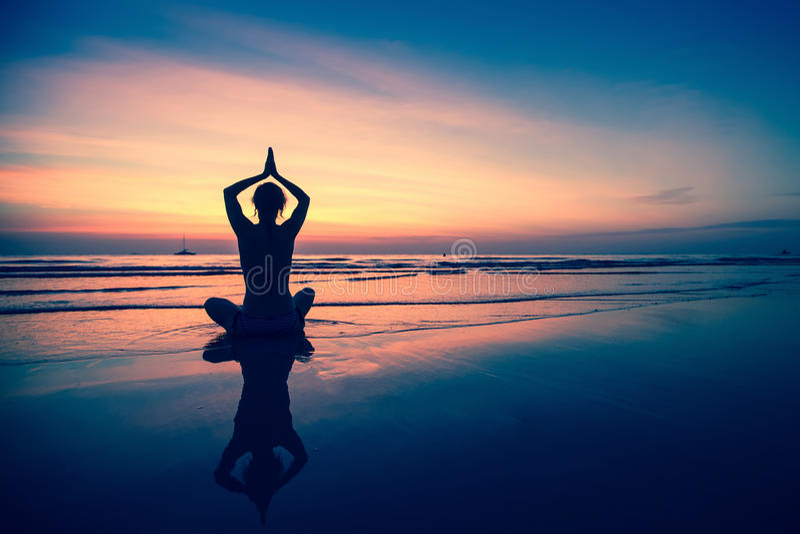 Yoga för ung kvinna för kontur praktiserande på stranden på den surrealistiska solnedgången relax royaltyfria bilder