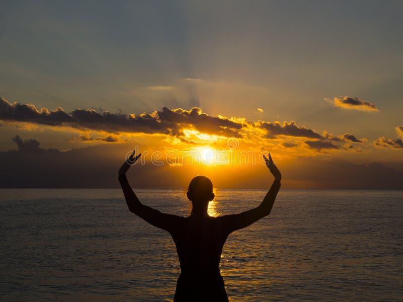 Yoga för ung kvinna för kontur praktiserande på stranden på solnedgången E arkivfoto
