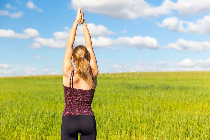 Yoga för ung kvinna som sträcker bakre sikt arkivfoton