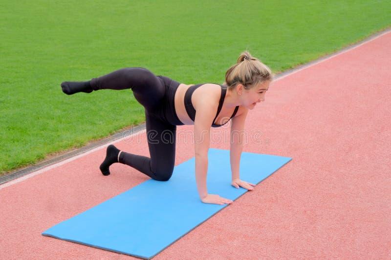 YOGA f?r viktf?rlust Den fulla kroppflickan går in för sportar i parkerar utomhus Övningar som sträcker och som förstärker muskle royaltyfri foto