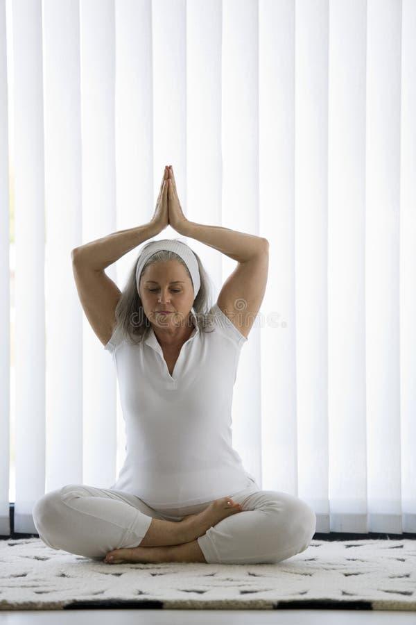 Yoga facente senior fotografia stock