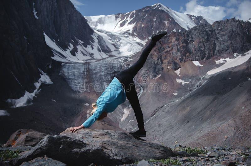 Yoga faisant blond sur une grande roche sur un fond de glacier Le concept du voyage et du sport photo stock