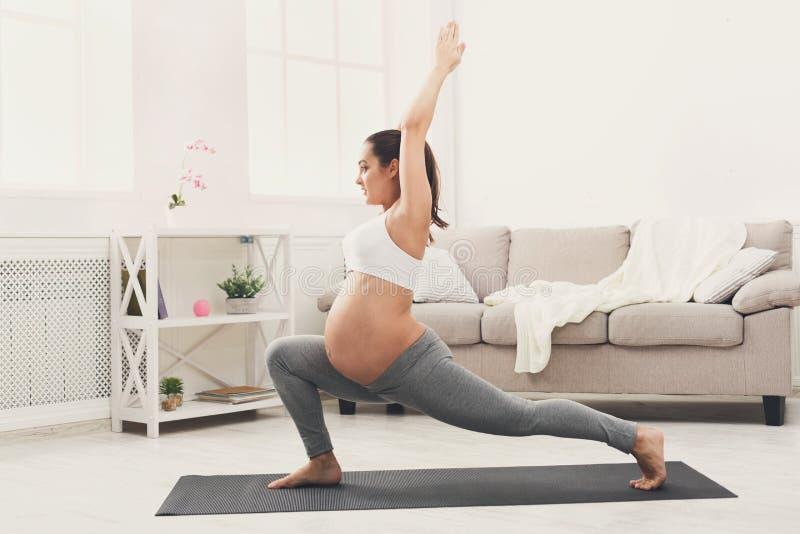Yoga felice di addestramento della donna incinta nella posa dell'eroe immagine stock