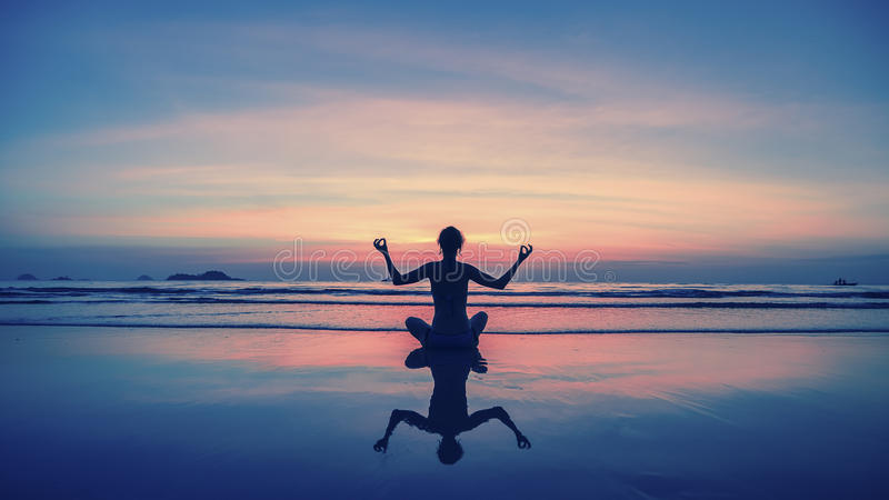 Yoga, fitness, healthy lifestyle. Silhouette meditation girl on the background of the stunning sea and sunset. stock image