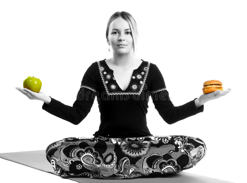 Yoga food concept. Women sitting with fruits and hamburger in hands stock photos