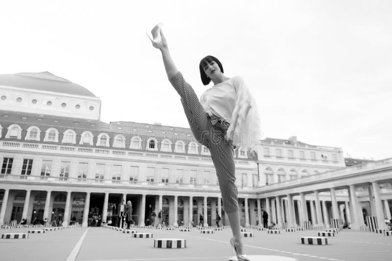 Yoga, forma fisica dei pilates, sport a Parigi, Francia Gamba spaccata della donna sul quadrato Bellezza di modo, stile di vita d fotografie stock