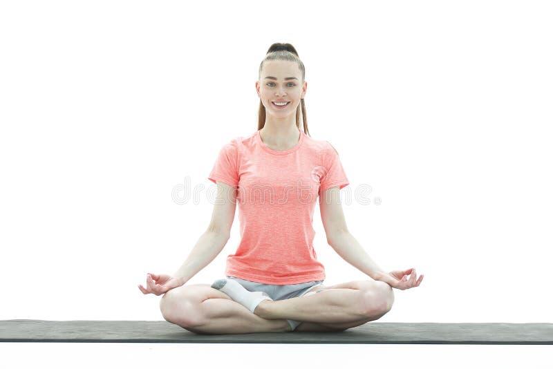 yoga Frau, die Yoga gegen wei?en Hintergrund meditiert und tut stockfotografie