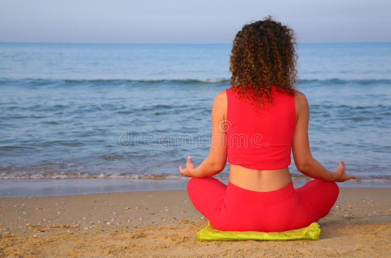 Yoga girl on beach from back stock photography