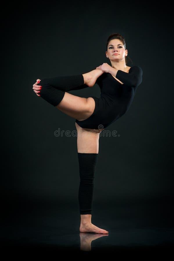 Yoga girl on black background exercises stretching stock photo