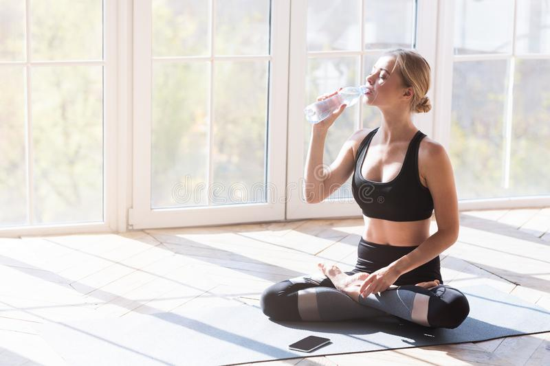 Yoga girl having break while morning exercising, drinking water. Yoga girl having break while morning exercising in sun light, drinking water over panoramic stock image