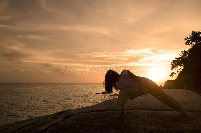 Yoga girl performing yoga pose on a beach royalty free stock images