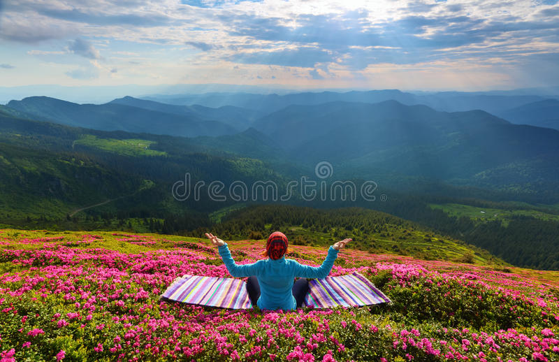 Yoga girl is sitting on the striped rug in meditation. royalty free stock photo