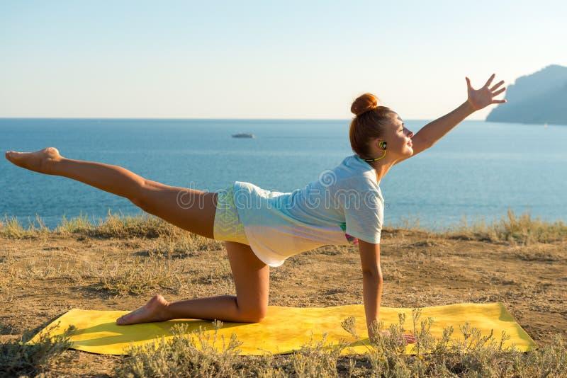 Yoga girl with wireless headphones royalty free stock image