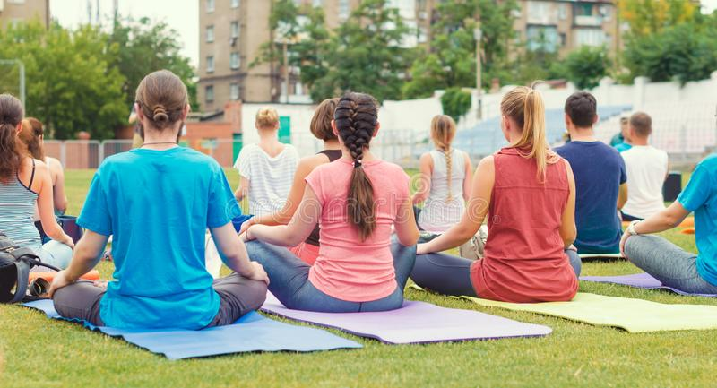 Yoga group of young girls and men meditates sitting in the park royalty free stock photography