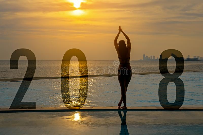 Yoga Happy new year card 2018. Silhouette woman practicing yoga on swimming pool standing as part of Number 2018 near the beach at royalty free stock image