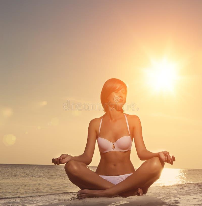 Yoga hermosa de la muchacha en la playa en la puesta del sol imágenes de archivo libres de regalías