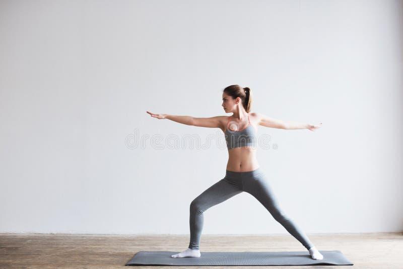 Yoga hermosa joven que presenta en la estera dentro foto de archivo