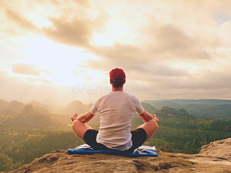 Yoga het praktizeren bij bergtop met luchtmening van de bergvallei Lange sportman het praktizeren yoga stock foto