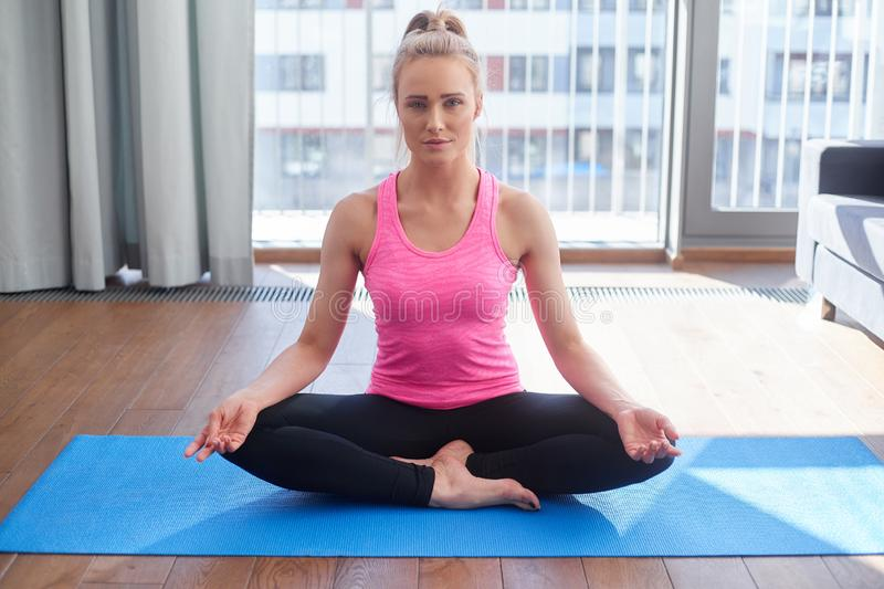 Attractive young blonde woman exercising and sitting in yoga lotus position. Yoga at home. Attractive young blonde woman exercising and sitting in yoga lotus royalty free stock photography