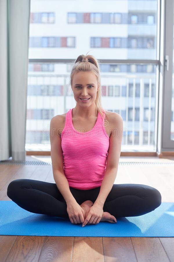 Attractive young blonde woman exercising and sitting in yoga lotus position. Yoga at home. Attractive young blonde woman exercising and sitting in yoga lotus royalty free stock image