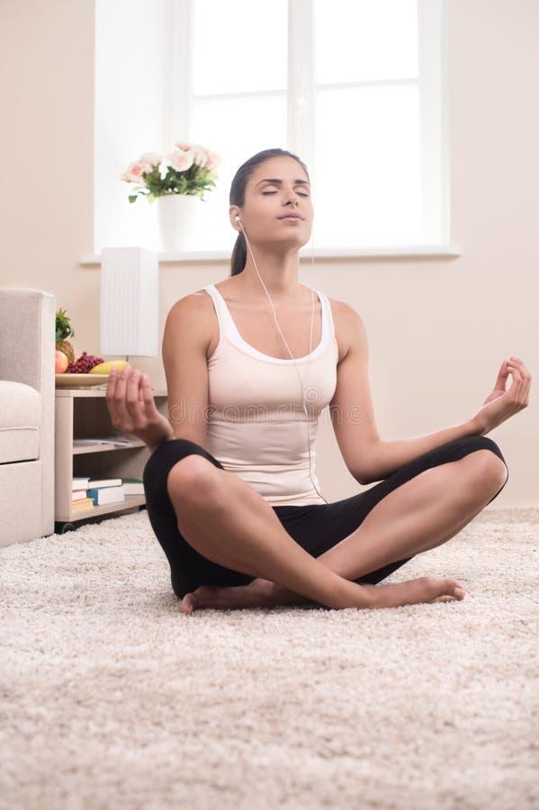 Yoga at home. Beautiful young women meditating at home stock photography