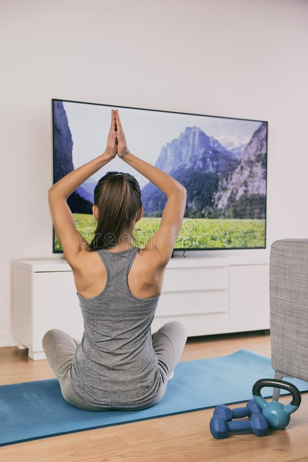 Yoga at home fitness class streaming on TV app online woman training in living room on exercise mat meditating alone - workout. Lifestyle royalty free stock image