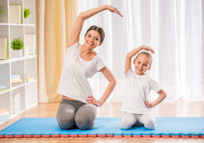 Yoga at home. Mother and daughter doing yoga exercises on rug at home stock photography