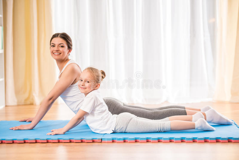 Yoga at home. Mother and daughter doing yoga exercises on rug at home royalty free stock photo