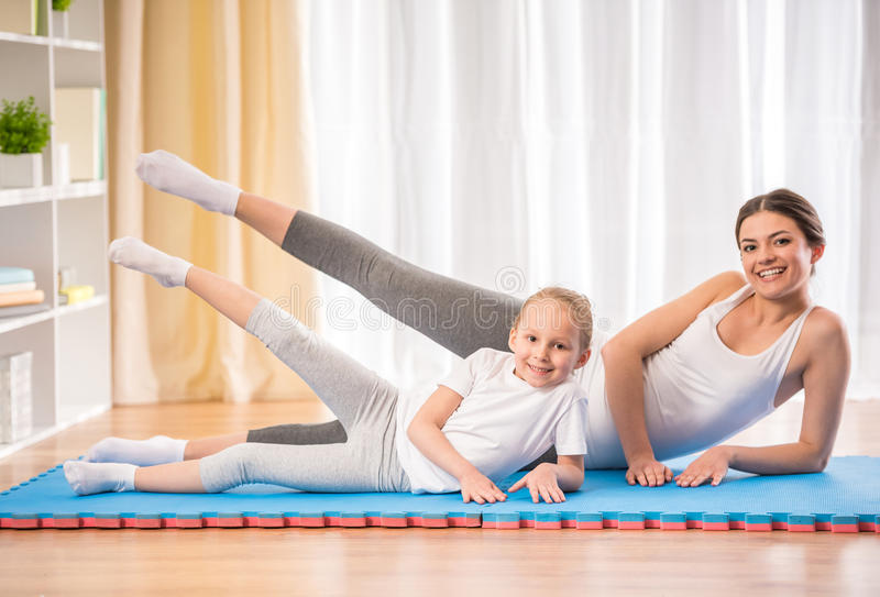 Yoga at home. Mother and daughter doing yoga exercises on rug at home royalty free stock image