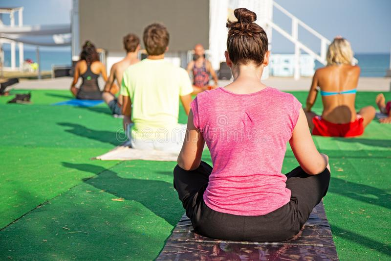 Yoga i parkerar, den unga kvinnan som gör övningar med gruppen av blandat ålderfolk royaltyfri foto