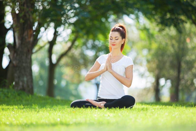 Yoga im Freien Die gl?ckliche Frau, die Yoga?bungen tut, meditieren im Park Yogameditation in der Natur Konzept des gesunden Lebe lizenzfreie stockfotos