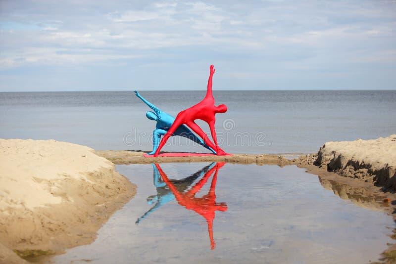 Yoga im Kaleidoskop am Strand lizenzfreie stockfotos