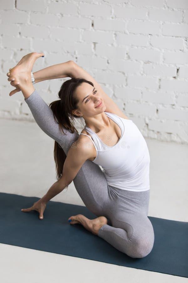 Yoga Indoors: Sundial yoga Pose. Beautiful smiling young woman working out indoors, doing yoga exercise on blue mat, sitting in Parivrtta Surya Yantrasana stock images