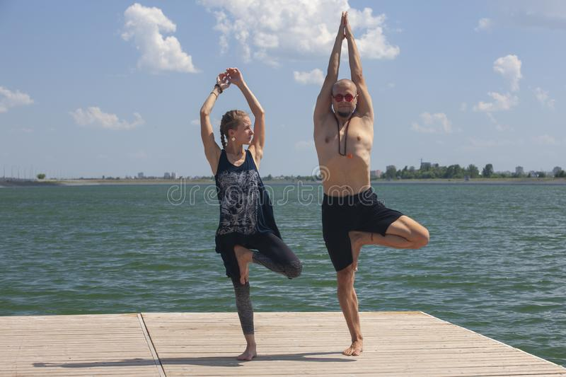 Yoga inspiration. Top view - couple of cheerful healthy beautiful slim man and woman are doing virabhadrasana. Yoga inspiration. Top view - couple of cheerful stock image