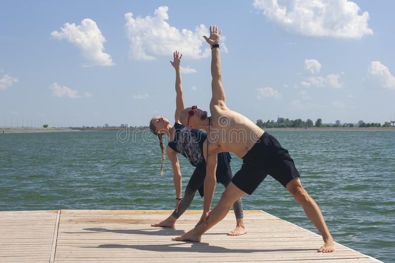 Yoga inspiration. Top view - couple of cheerful healthy beautiful slim man and woman are doing virabhadrasana. Yoga inspiration. Top view - couple of cheerful royalty free stock photography